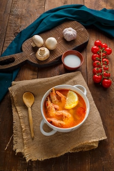 Soupe tom yam aux crevettes et lait de coco sur une table sur des planches en bois près des champignons au lait et des tomates. photo verticale