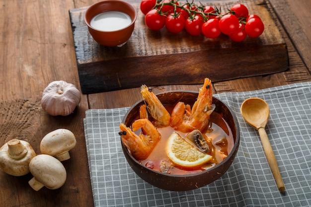 Soupe tom yam aux crevettes et lait de coco sur la table sur une serviette à carreaux à côté de légumes et d'une cuillère en bois. photo horizontale