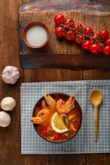 Soupe tom yam aux crevettes et lait de coco sur une table sur une serviette à carreaux à côté de légumes et d'une cuillère en bois. photo verticale