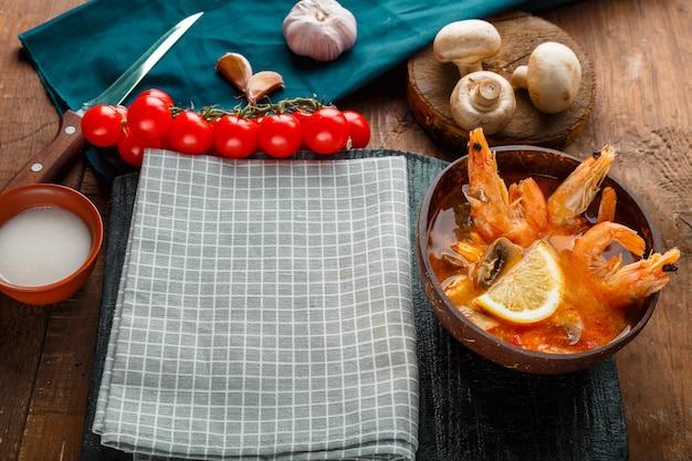 Soupe tom yam aux crevettes et lait de coco sur la table sur une serviette à carreaux près des ingrédients et d'une cuillère. espace de copie. photo horizontale