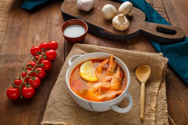 Soupe tom yam aux crevettes et lait de coco sur une table sur une serviette à côté de champignons au lait de coco et de tomates. photo horizontale