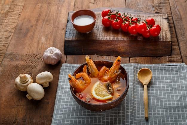 Soupe tom yam aux crevettes et lait de coco sur la table sur une serviette à côté du lait et d'une cuillère en bois. photo horizontale