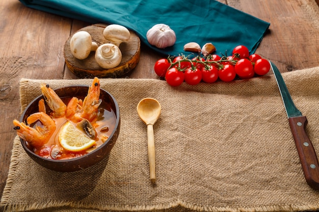 Soupe tom yam aux crevettes et lait de coco sur la table sur une serviette à côté des ingrédients et une cuillère en bois. espace de copie. photo horizontale