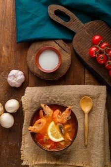Soupe tom yam aux crevettes et lait de coco sur une table sur une serviette en lin à côté de légumes et d'une cuillère en bois. photo verticale