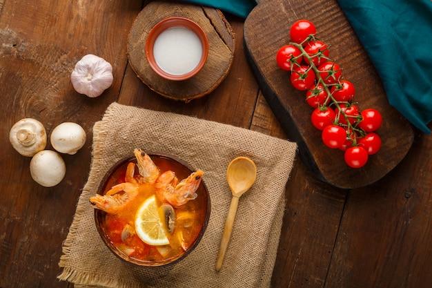 Soupe tom yam aux crevettes et lait de coco sur la table sur une serviette en lin à côté de légumes