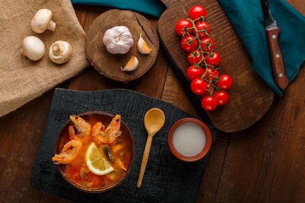 Soupe tom yam aux crevettes et lait de coco sur une table sur un tableau noir et une cuillère. photo horizontale