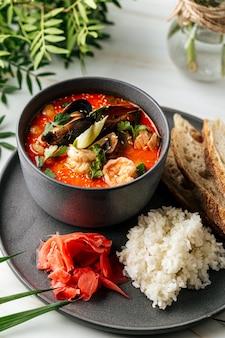 Soupe tom yam aux fruits de mer et riz avec toasts