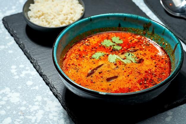 Soupe tom yum asiatique classique aux crevettes, champignons shiitake, poulpe, tomates et riz dans une assiette en arrière-plan. service au restaurant. soupe chinoise rouge