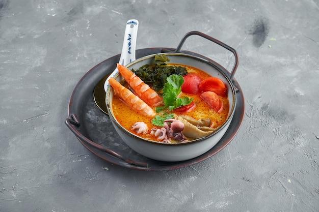 Soupe tom yum asiatique classique avec crevettes, champignons shiitake, poulpe, tomates et riz dans une assiette à la surface. service au restaurant. soupe chinoise rouge