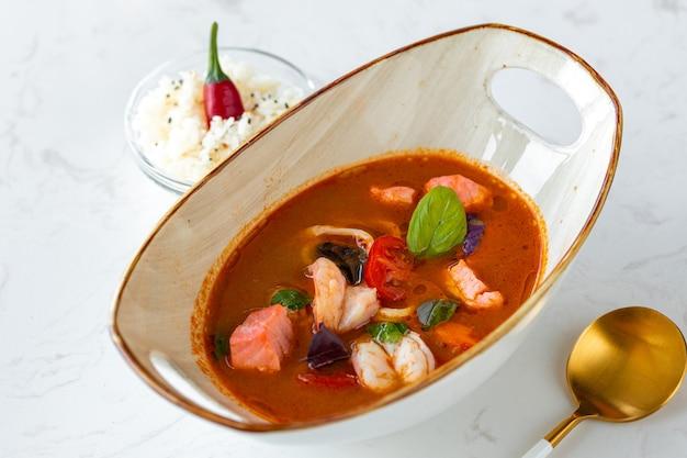 Soupe tom yum asiatique dans un bol sur une table grise