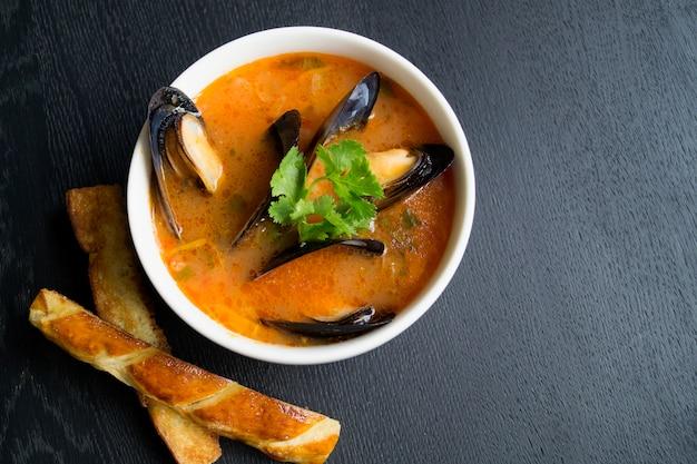 Soupe de tomates aux moules. avec des croûtons frits sur un fond noir.