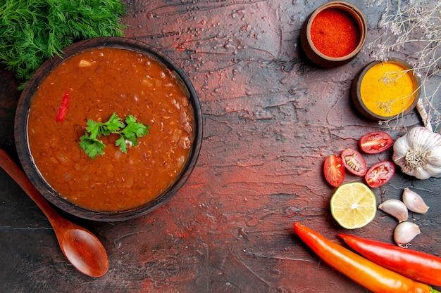 Soupe de tomates classique dans un bol brun et différentes épices ail citron sur table de couleurs mélangées