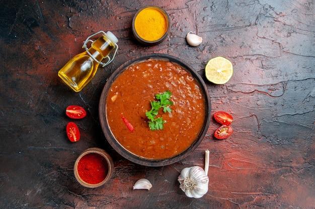 Soupe de tomates dans un bol brun et différentes épices ail citron sur table de couleurs mélangées