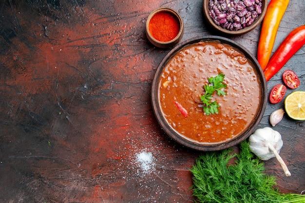 Soupe de tomates dans un bol brun et différentes épices ail citron et verts sur table de couleurs mélangées