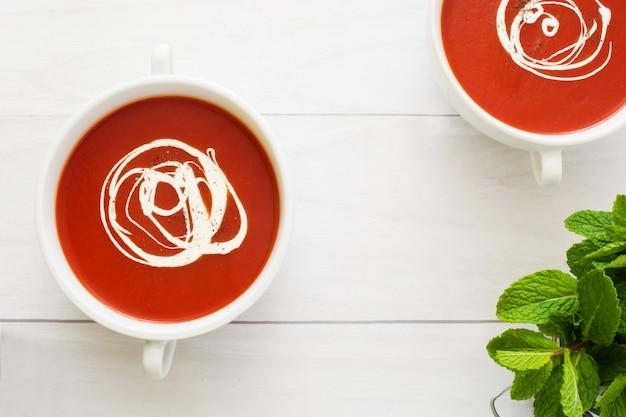 Soupe de tomates fraîches dans un bol blanc sur la table en bois blanc vue de dessus copie espace