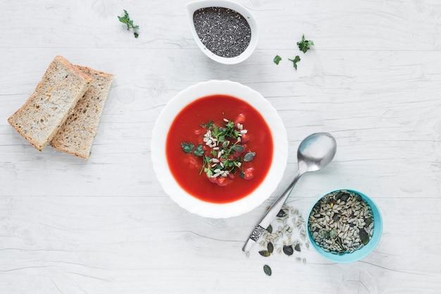 Soupe de tomates garnie de graines de chia et de citrouille avec une tranche de pain sur une table en bois blanche