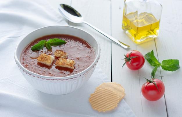 Soupe de tomates gaspacho avec croûtons, deux tomates rouges, huile d'olive et une cuillère sur un fond en bois blanc.