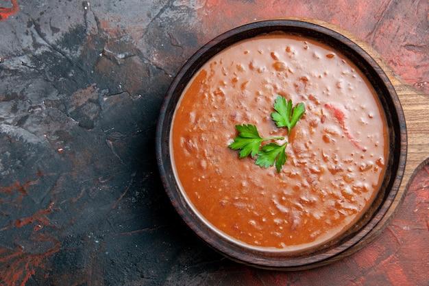 Soupe de tomates sur une planche à découper brune sur le côté droit d'une table de couleurs mélangées
