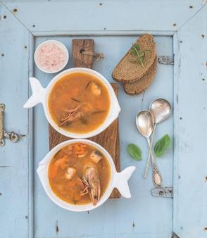 Soupe de tomates poisson bouillabaisse française avec filet de saumon, crevettes et épices sur une planche en bois rustique sur mur bleu