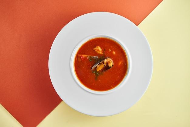 Soupe de tomates rouges aux fruits de mer, moules et crevettes dans une assiette blanche sur une surface colorée.