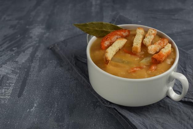 Soupe traditionnelle aux pois cassés jaunes avec mandrins durs en plaque blanche avec poignées. soupe végétarienne sur fond gris avec espace de copie.
