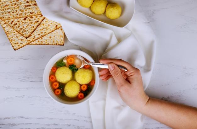 Soupe traditionnelle de balle de matsa, plat juif de pâque, servi avec de la matsa, une haggadah de pâque