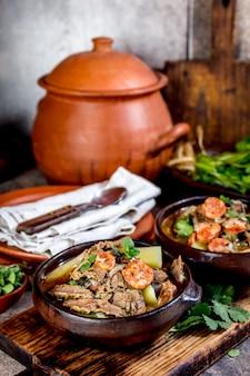 Soupe traditionnelle chilienne avec viande grillée, oignons et pommes de terre servis dans des assiettes en argile