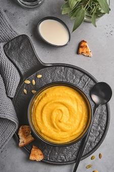 Soupe traditionnelle à la citrouille avec une texture soyeuse et crémeuse avec des feuilles de sauge et du poivron rouge dans une assiette ou un bol noir. vieux fond gris. espace de copie. maquette. vue de dessus, mise à plat.