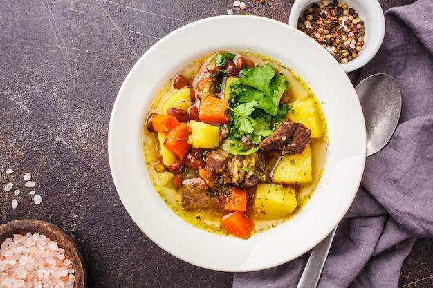 Soupe traditionnelle eintopf avec viande, haricots et légumes dans une assiette blanche.