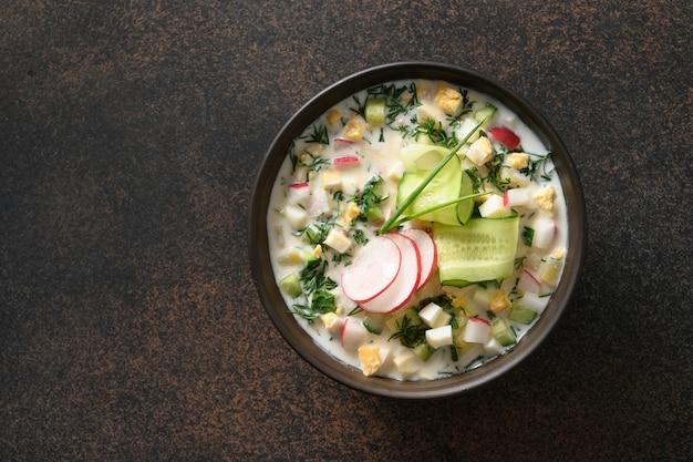 Soupe traditionnelle russe d'okroshka aux légumes froids avec concombre haché, radis, pomme de terre, œufs durs et kéfir ou airan, eau gazéifiée isolée sur fond marron. vue de dessus.