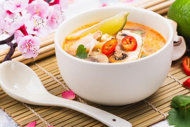 Soupe traditionnelle tom yum avec une branche de sakura en fleurs sur une table en pierre blanche
