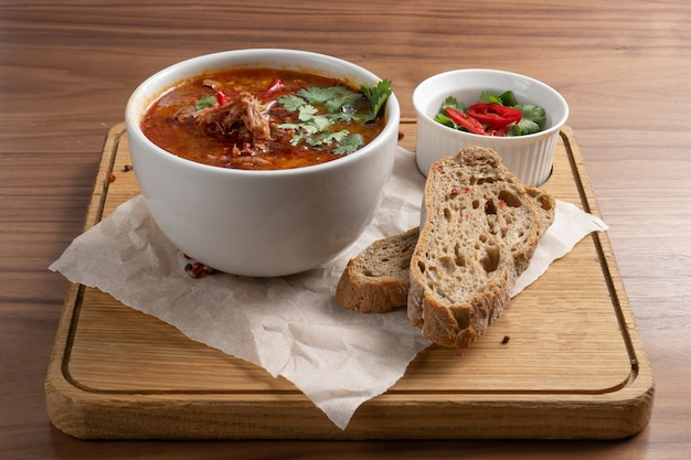 Soupe traditionnelle ukrainienne à base de betteraves, de légumes et de viande avec du pain sur une table en bois.