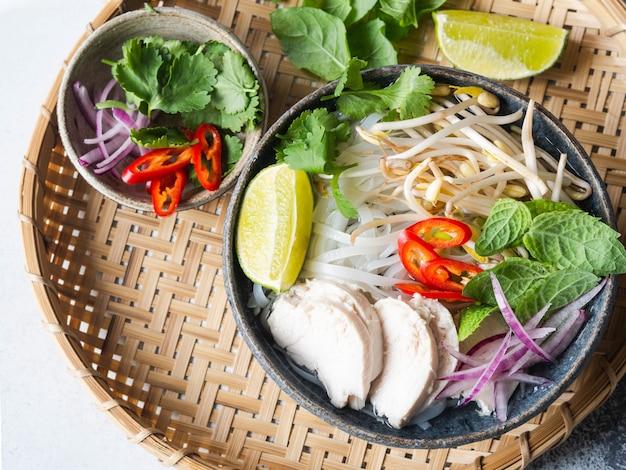 Soupe traditionnelle vietnamienne - pho ga dans un bol avec poulet et nouilles de riz