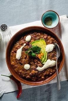 Soupe végétalienne au chili sans viande, aux haricots pinto et à l'avocat, servie avec du yaourt à base de soja sur des nappes en lin. alimentation équilibrée