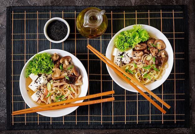 Soupe végétalienne aux nouilles avec tofu, champignons shiitake et laitue dans un bol blanc.