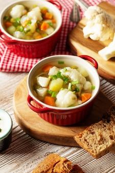 Soupe végétarienne de chou-fleur dans une casserole, pain, chou-fleur cru