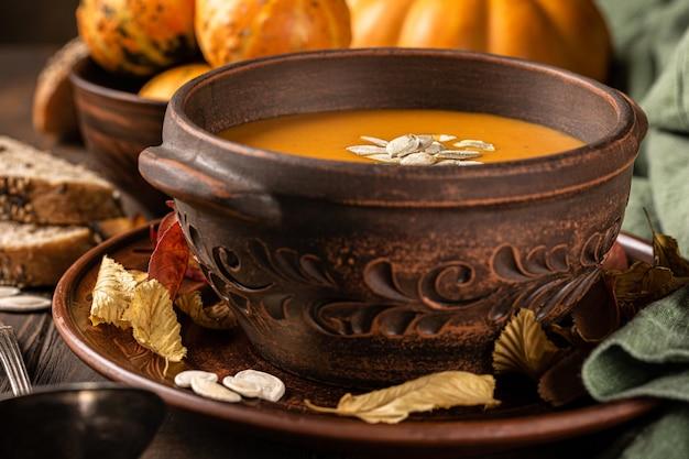 Soupe végétarienne à la citrouille et aux carottes rôties à l'automne avec des graines dans un vieux bol brun