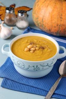 Soupe végétarienne à la crème de citrouille d'automne avec pois chiches sur bleu clair