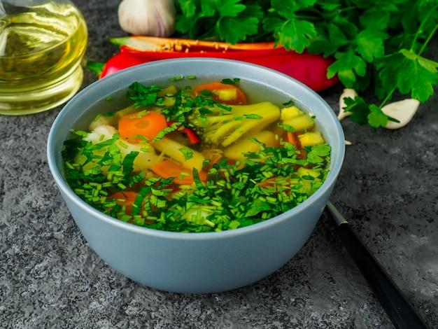 Soupe végétarienne diététique de légumes sains de printemps, fond béton gris