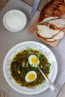 Soupe végétarienne à l'oseille avec œuf, servie avec de la crème sure et du pain. style rustique.