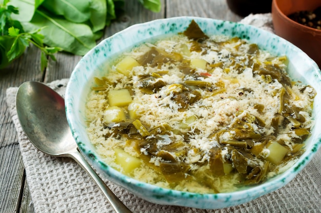 Soupe végétarienne simple à base d'oseille, de pommes de terre et d'œufs battus sur un fond en bois ancien.