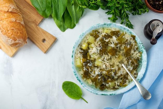 Soupe végétarienne simple à l'oseille, pommes de terre et œufs battus sur une surface légère
