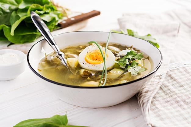 Soupe verte d'oseille dans un bol blanc