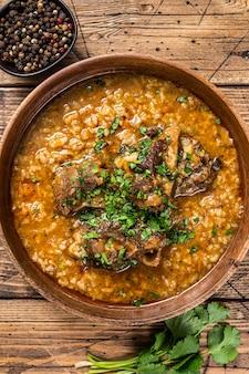 Soupe de viande d'agneau kharcho géorgienne avec riz, tomates et épices dans un bol en bois. fond en bois. vue de dessus.