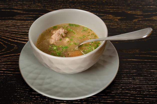 Soupe à la viande et aux herbes dans un bol gris sur une table en bois sombre. plat géorgien chikhirtma.