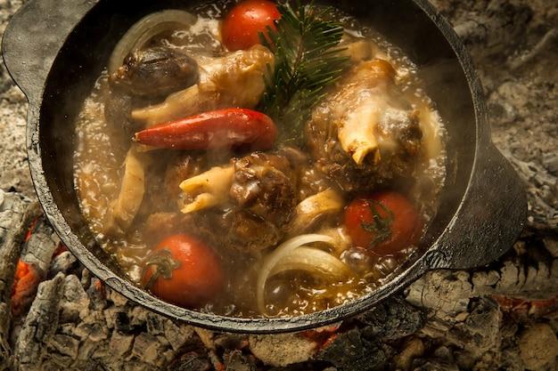 Soupe de viande aux légumes préparée sur des charbons ardents. le plat est cuit et fumé au charbon de bois