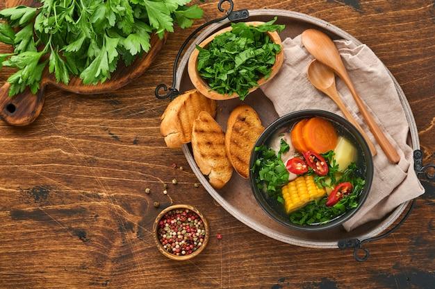 Soupe de viande chilienne avec pampkin, maïs, coriandre fraîche et pommes de terre sur fond de table en bois ancien. cazuela. nourriture latino-américaine.
