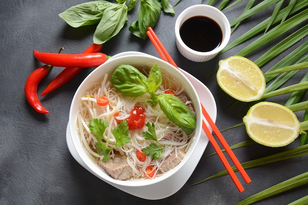Soupe vietnamienne pho bo aux herbes, boeuf, nouilles de riz, chili et germes de soja