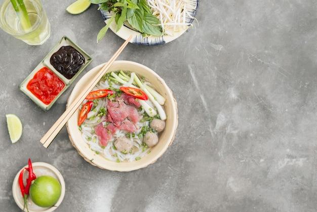 Soupe vietnamienne traditionnelle pho bo aux herbes, viande, nouilles de riz, bouillon. pho bo dans un bol avec des baguettes, une cuillère. espace pour le texte. vue de dessus. soupe asiatique pho bo sur fond de table en bois. soupe vietnamienne