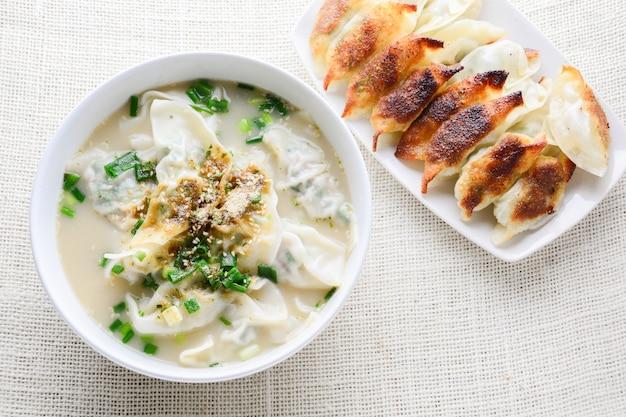 Soupe wonton aux oignons nouveaux servie dans un bol blanc, mise au point sélective